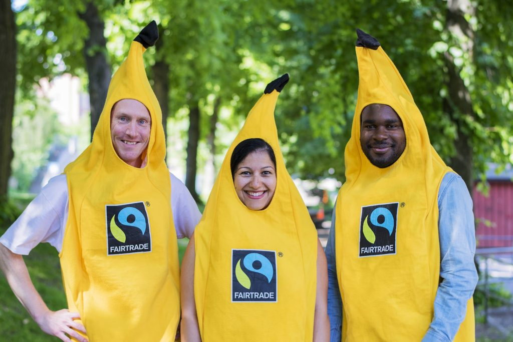 Three people in banana costumes, outdoor image