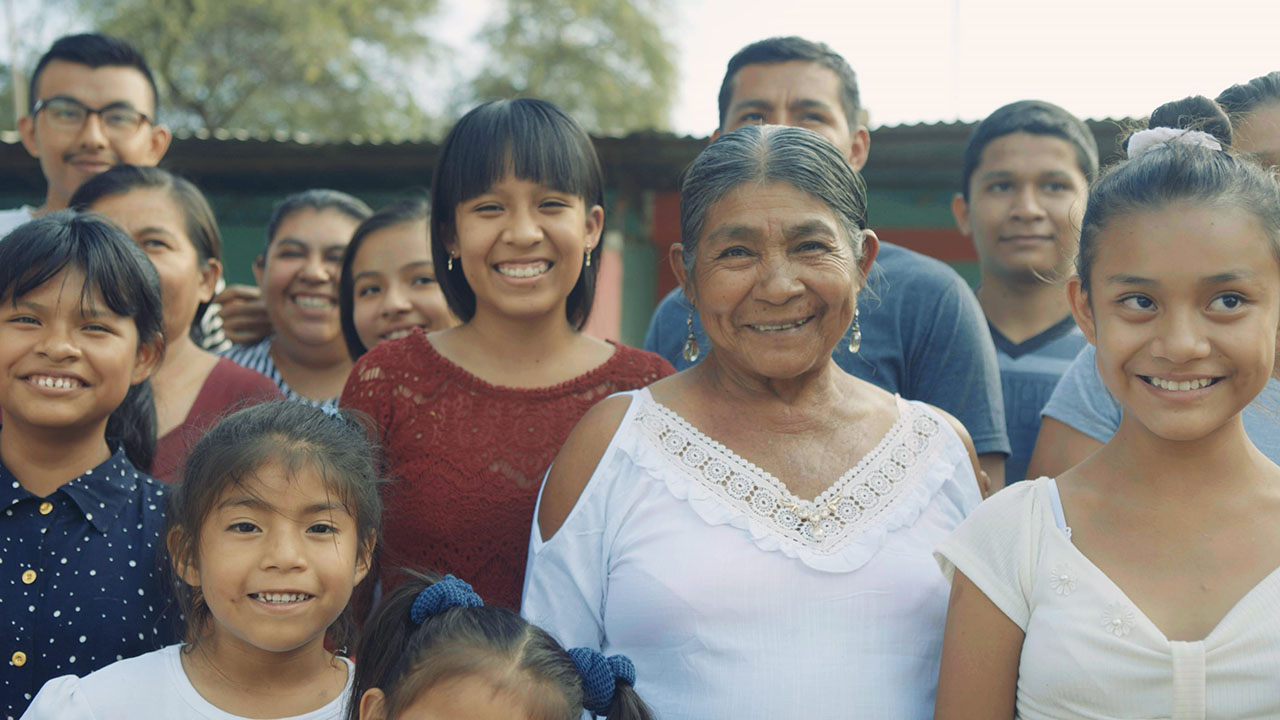 Justa More, also known as Dona Justa, poses with her granddaughter Leydi Jimena and the rest of her family in Saman, Peru.