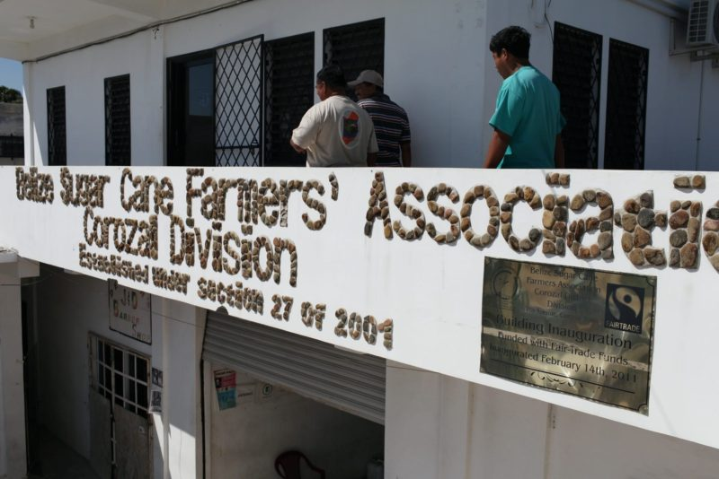 """The facade of the Belize Sugar Cane Farmers Association (BSCFA) office in Corozal displays a plaque that reads: """"Building Inauguration Funded with Fairtrade Funds on February 14th, 2011."""""""